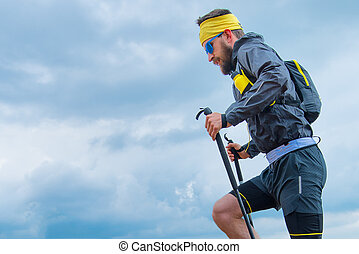 Man practicing trail running in the mountains with the sky background