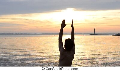 Man practicing yoga at dawn on the beach
