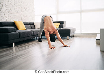 Man Practicing Yoga At Home Doing Sun Salutation Routine -...