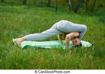 Man practicing yoga in the green park on a summer day