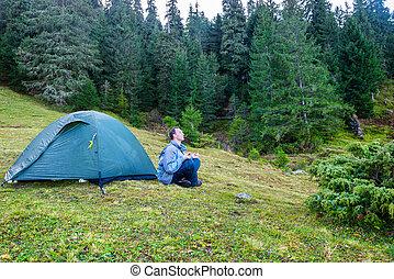 Man practicing yoga near blue camping tent
