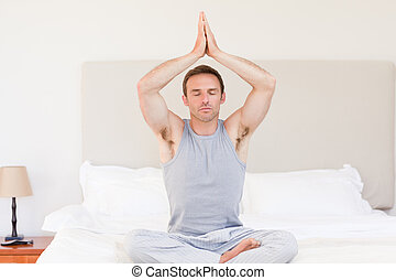 Man practicing yoga on his bed
