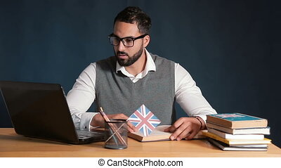 Man Practises Reading with Tablet and Book - Bright handsome...