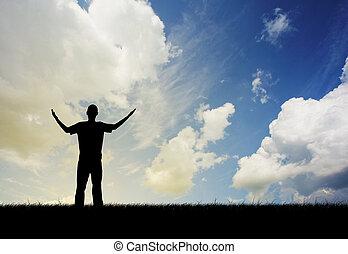 Man praising - Man in silhouette lifting hands in praise in...