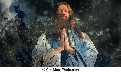 Man praying against clouds - Yogi sitting in meditation on...
