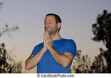 Man praying alone at dusk.