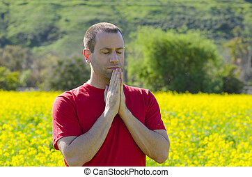 Man praying alone in a an open field in nature.
