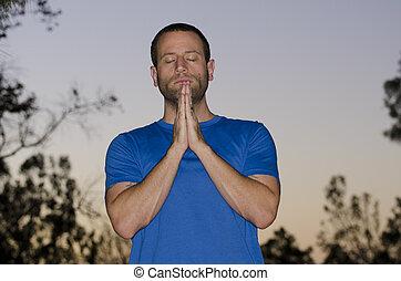 Man praying at night fall outdoors.