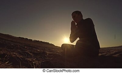 Man praying at sunset god sitting silhouette sun sunlight...
