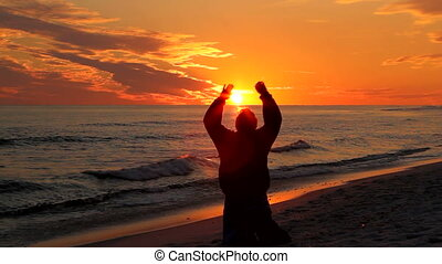 Man, with arms raised toward the heavens, prays at the beach at sunset.