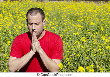 Man praying in a field of yellow flowers.