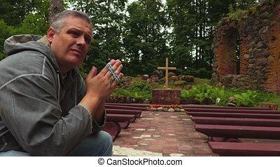 Man praying in church ruins