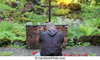Man praying in outdoors church opposite the cross