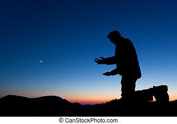 Man Praying - Man praying on the summit of a mountain at sun...