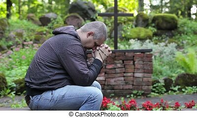 Man praying on bench with the rosary at outdoors church