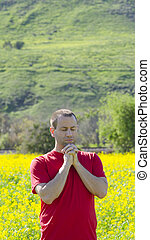 Man praying outside in nature alone.