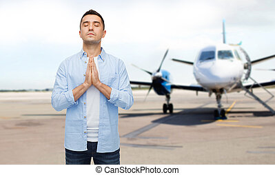 man praying over airplane on runway background