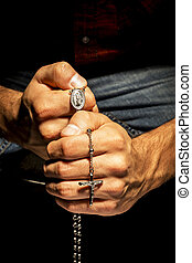 Man praying - Praying Hands with rosay in black background