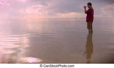 """""""A middle aged man praying while standing in an ocean with crashing waves in the far distance during sunrise or sunset, side view hand held."""""""
