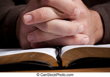Man Praying with Bible - Man's hands folded and praying over...