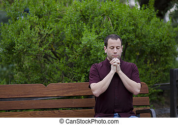 Man praying with clasped hands on a bench outside.