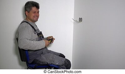 Man prepare wires to connect socket rosette frames in plasterboard wall holes