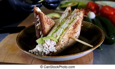 Man prepares lunch, serves grilled bread sandwich snack on...