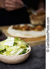 closeup of a bowl with chopped lettuce on a table, and a young man in the background preparing a durum or a burrito, with chicken meat cooked with different vegetables, such as onion or red pepper