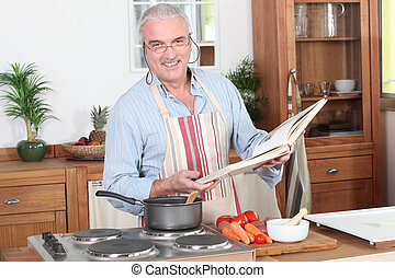 Man preparing a meal with the help of a cookbook