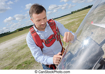 man preparing a small sport airplane at the airport