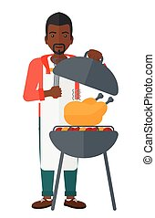Man preparing barbecue. - An african-american man cooking...