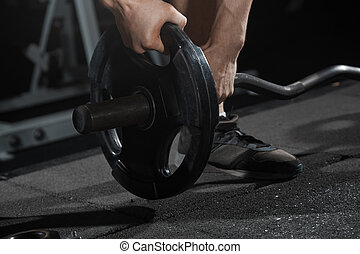 Man preparing barbell at gym