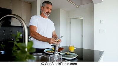 Man preparing breakfast in kitchen at home 4k