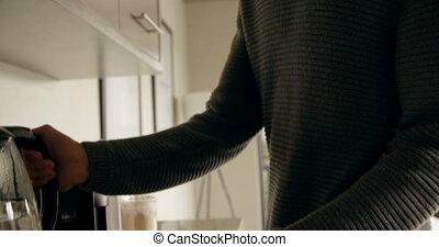 Man preparing coffee in kitchen 4k