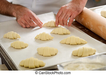 Man preparing croissants for baking, placing them on a tray
