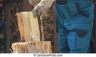 Man Preparing House for Winter - House owner splitting logs...