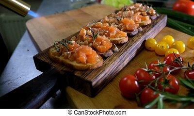 Man preparing Italian bruschetta with baked tomatoes, basil...