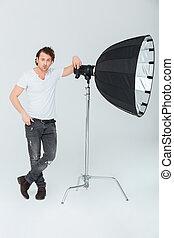 Man preparing lighting equipment - Full length portrait of a...