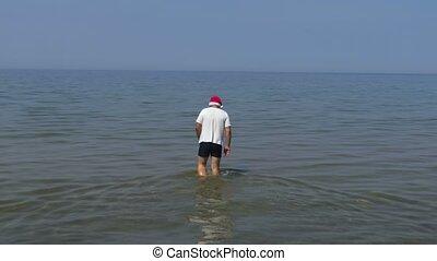 Man preparing to go for a swim in the sea