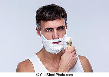 Man preparing to shave, applying shaving foam with a shaving brush