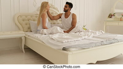 Man present woman greeting card gift sitting bed couple love home bedroom