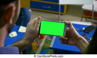 Man presenting to a woman and holding smart phone with green screen