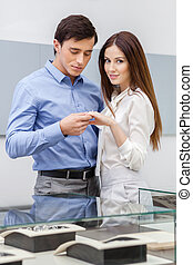 Man presents engagement ring to his woman at jeweler's shop....