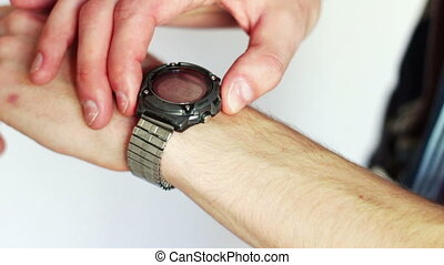 Man presses a button on the electronic wristwatch his arm.