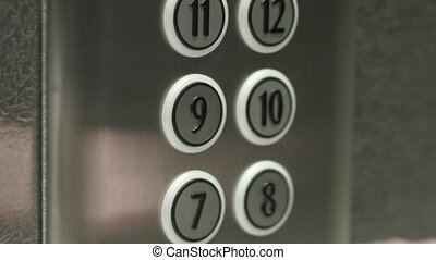 Man presses a button the ninth floor in an elevator - Man...