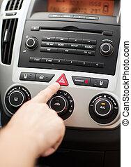 man pressing car hazard warning button - transportation and...
