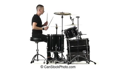Man professionally plays percussion instruments . White background. Side view. Slow motion