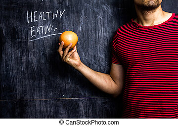Man promoting healthy eating in front of blackboard