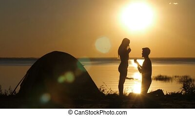 Man proposing beloved woman on the beach at sunset -...