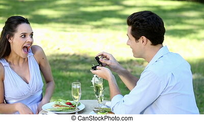 Man proposing marriage to his shocked girlfriend